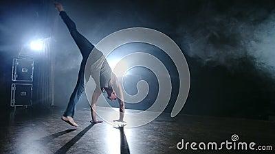 Ballet moderno, un hombre de una posición sentada en el escenario salta de vuelta con rotación en un escenario oscuro en el humo  almacen de video