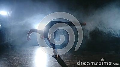 Ballet moderno, un hombre de una posición sentada en el escenario salta de vuelta con rotación en un escenario oscuro en el humo  metrajes