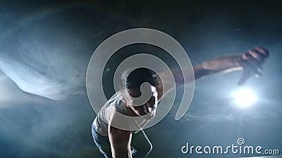 Ballet moderno, un hombre desde una posición sentada en el escenario salta a una cámara en un escenario oscuro almacen de video