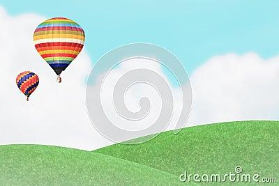 Ballons over grass hill.