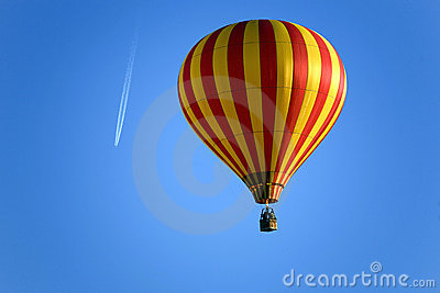Balloon and an airplane on the blue sky