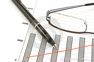 Ballpoint pen and glasses on earning graphs