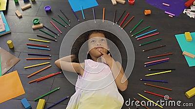 Bambina afroamericana piacevole che si trova sul pavimento e sulle feste future di progettazione video d archivio