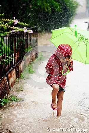 Bambina che cammina nella pioggia