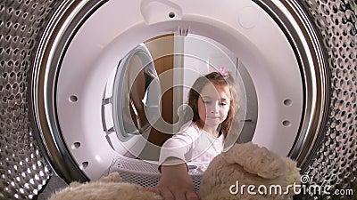 Bambina che carica il suo giocattolo farcito alla lavatrice video d archivio