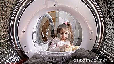 Bambina che carica il suo giocattolo farcito alla lavatrice archivi video