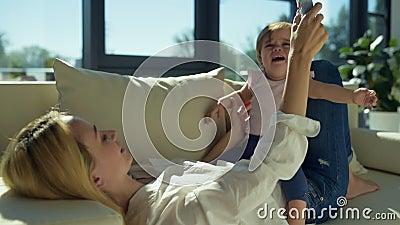 Bambina deludente con la giovane madre sul sofà video d archivio