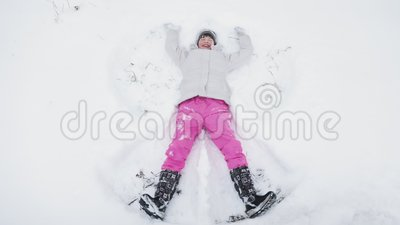 Bambina sveglia felice che fa angelo della neve video d archivio