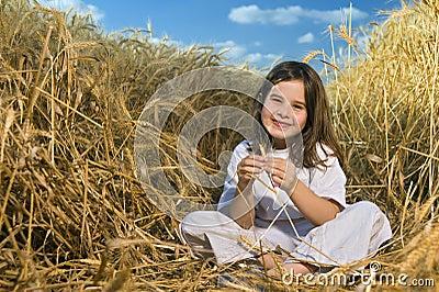 Bambina in un campo di frumento