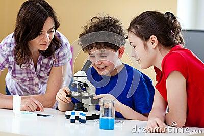 Bambini che per mezzo del microscopio