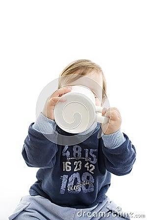 Bambino che beve con la grande tazza