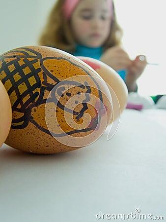 Bambino che decora le uova di Pasqua
