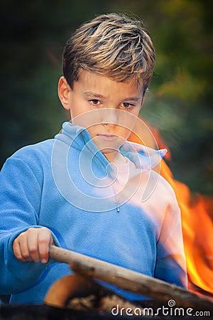 Bambino che fissa al fuoco di accampamento