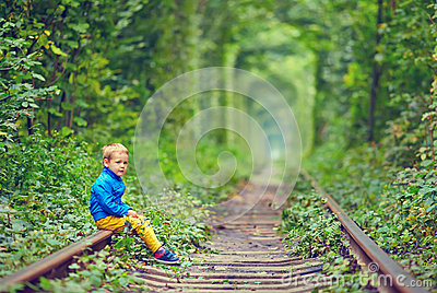 Bambino che si siede sulle rotaie in tunnel verde
