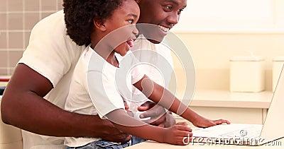 Bambino con suo usando del padre video online sul computer video d archivio