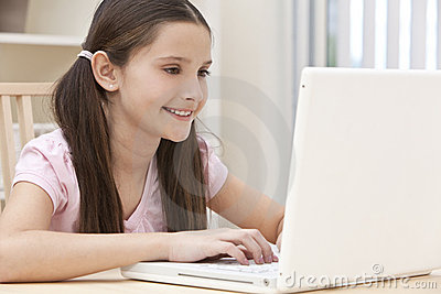 Bambino della ragazza che per mezzo del computer portatile nel paese