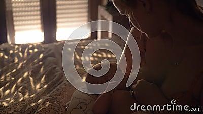 Bambino di allattamento al seno della madre in camera da letto archivi video