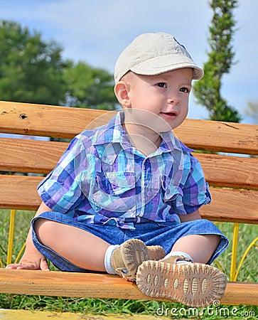 Bambino di divertimento che si siede sul banco