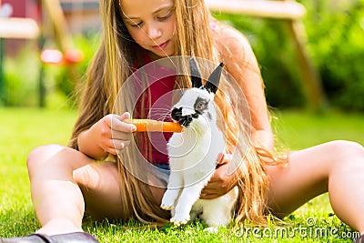 Bambino felice con l animale domestico del coniglietto a casa in giardino