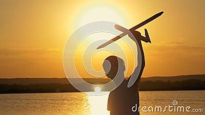Bambino felice su un fondo di un cielo e di un lago arancio di estate al tramonto, giocante con un aeroplano del giocattolo archivi video