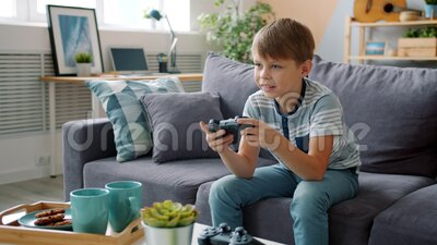 Bambino sorridente che gioca a videogioco da solo a casa e si diverte con un dispositivo figo video d archivio