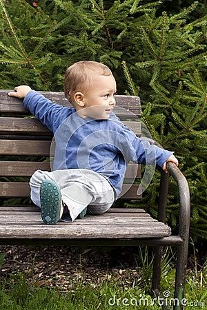 Bambino sul banco del giardino