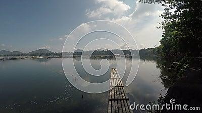Bambusowa tratwa unosi się na zanieczyszczającym jeziorze na chmurnym dniu zbiory