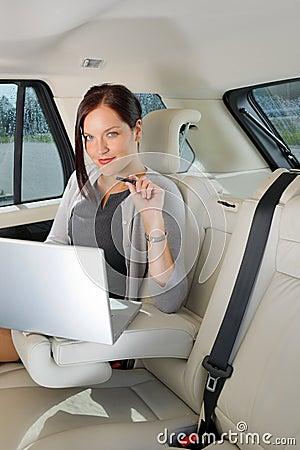 Banco traseiro executivo do carro do portátil do trabalho da mulher de negócios
