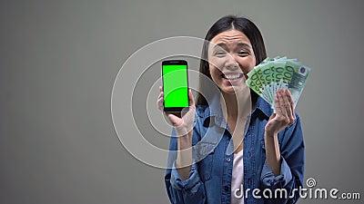 Banconote emozionanti dello smartphone e dell'euro della tenuta della giovane signora, vincitore di lotteria online stock footage