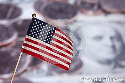 Bandeira americana sobre notas de banco e moedas dos E.U.