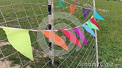 Bandeiras de triângulo coloridas na corda acenando no vento em um campo de futebol próximo ao portão durante o festival esportivo filme