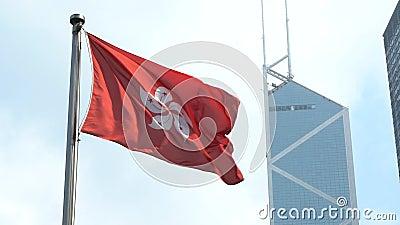 Bandiera del movimento lento di Hong Kong che ondeggia nel vento con la torre della banca di Cina stock footage