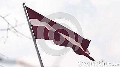 Bandiera lettone che fluttua nel livello del vento su nel cielo durante il tramonto dorato di ora - capitale di Riga, Lettonia -  stock footage