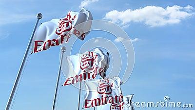 Bandiere d'ondeggiamento con il logo di Emirates Airlines contro il cielo, ciclo senza cuciture animazione dell'editoriale 4K archivi video