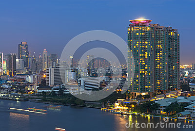 Bangkok cityscape. Bangkok river side with light of Yacht at twi