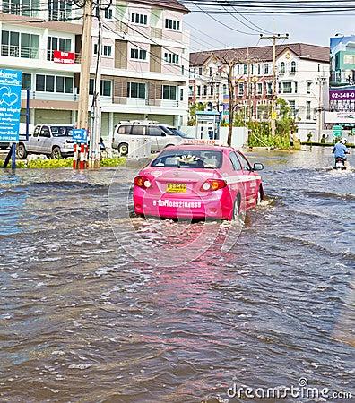 Bangkok-Nov 08 : Taxi drives in water flood road Editorial Photo