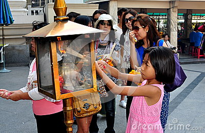 Bangkok, Thailand: Little Girl Lighing Incense Sticks Editorial Stock Photo