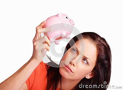 Banka przyglądającego pieniądze prosiątka nieszczęśliwa kobieta