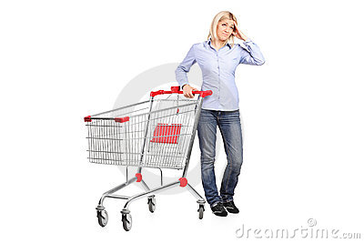 Bankrupt woman posing next to a shopping cart