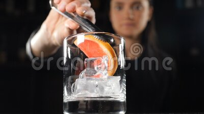 Bar in night club. Preparing alcohol drink with ice and fruit. Tongs put slice of orange into beverage. Cold cocktail. Served at bar counter in club. slow stock footage