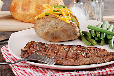 Barbecue steak with baked potato and cheese