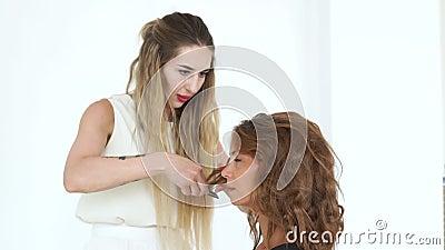 Barbeiro que usa o pente ao criar o penteado encaracolado à mulher bonita Cabeleireiro que faz o penteado à mulher atrativa video estoque