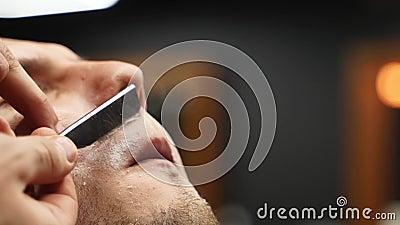Barbería profesional de barba de cliente con navaja de afeitar recta Barba cortada con una cuchilla anticuada en la barbería almacen de video