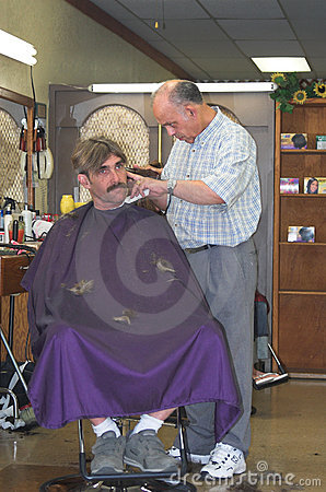 Barber cutting man s hair.