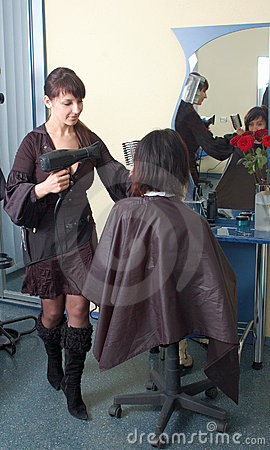 Barber makes a hair-dress to the young brunette