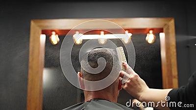 Barber pulveriza agua sobre el cabello del cliente antes de cortarlo y estilizar en una barbería La peluquera se moja el pelo med metrajes