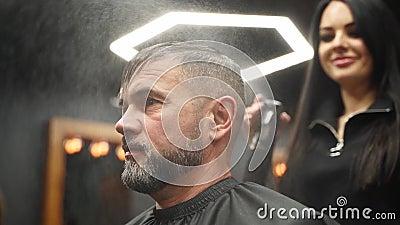 Barber pulveriza agua sobre el cabello del cliente antes de cortarlo y estilizar en una barbería La peluquera se moja el pelo med almacen de metraje de vídeo