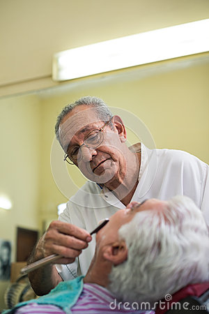 Barber with razor shaving client in barber shop