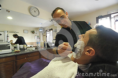 Barber shaving with Brush shaving foam to young man Editorial Photo