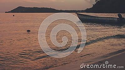 Barco de madeira local perto da praia durante o pôr do sol Dusk na ilha de Gam Ondas calmas na superfície do oceano e rolando par video estoque